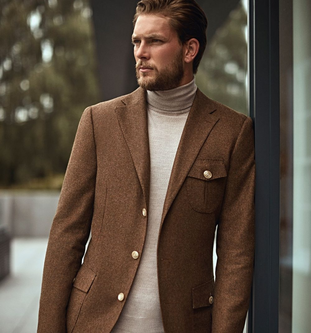 Model looking dapper in custom made brown structured jacket, layered over a cream turtleneck sweater