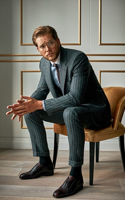 Man in smart pinstripe suit, designed by Senszio's custom tailors to be the perfect, bespoke fit for the individual.