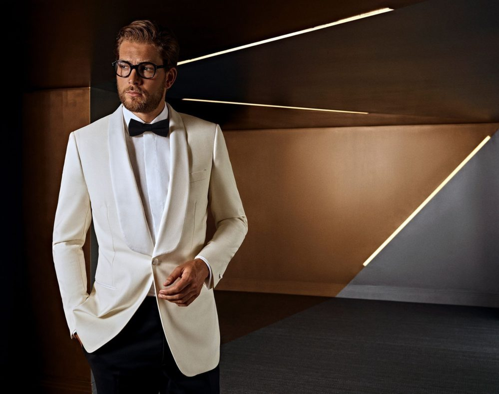 Man in stylish white tuxedo with black bow-tie, custom made occasion wear for men