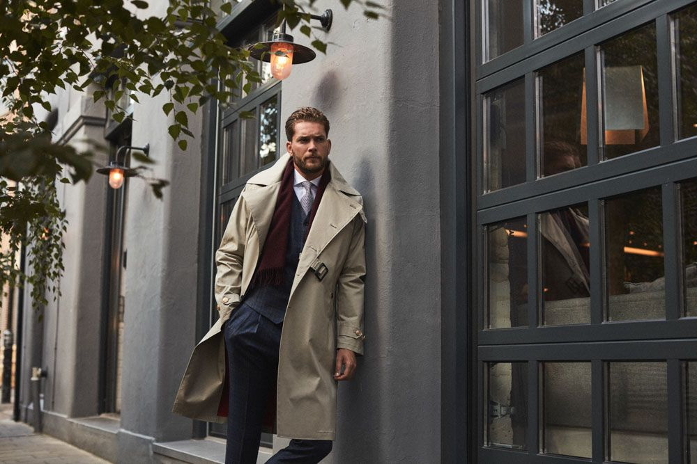 Man in custom tailored trench coat from Senszio, in classic camel and partnered with a suit.