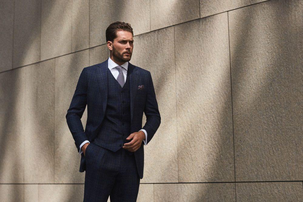 Model wearing sophisticated three-piece suit in dark navy, custom made to measure by Senszio