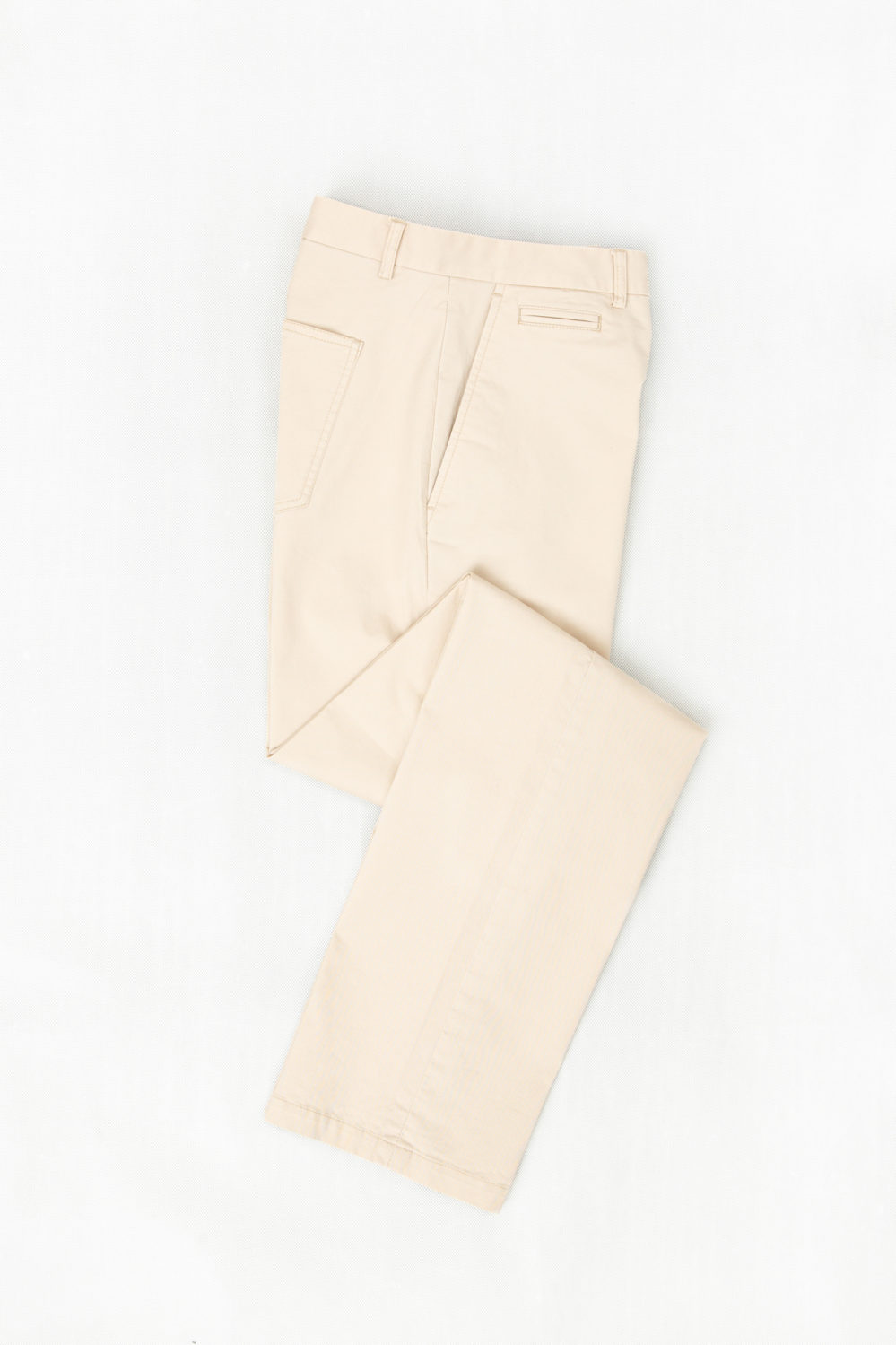 Flat lay of cream colored chinos, which can be custom tailored to your fit and frame