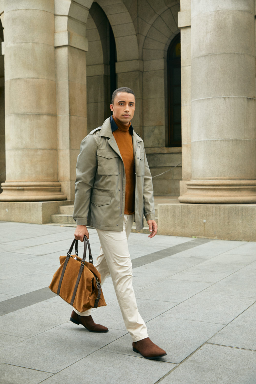 Model in Senszio custom tailored casual wear, including cream chinos and a field jacket