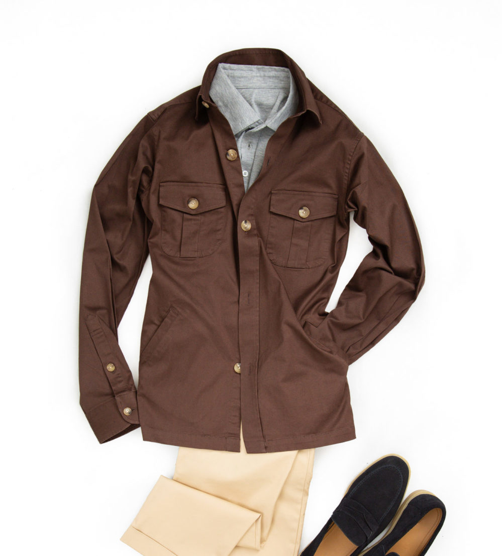 Flat lay of brown shirt jacket, also known as an overshirt, partnered with a grey polo shirt