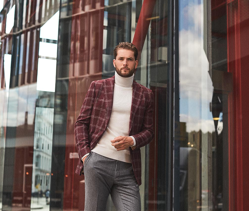 Man in custom tailor check print casual sports jacket, worn over a smart cream roll-neck sweater